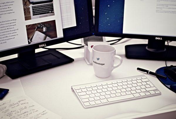 机の上のディスプレイとキーボードとコーヒー