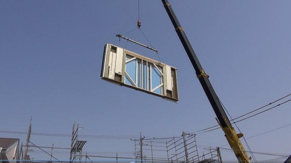 家の建築 クレーンで壁を運ぶ