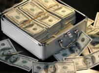 箱一杯の100ドル紙幣があふれて外に10枚ほど散っている